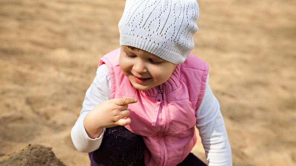 Barn + sand = sant. Sandlek er gøy, men selv om sand sjelden er skadelig å spise, kan det være lurt å begrense inntaket. Foto: Shutterstock