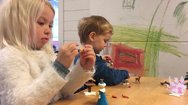 Ella (5 år) i dyp konsentrasjon med Playmobil kongelig skøytetur-kalenderen. Christian (2 år) i full lek med de små dyrene.
