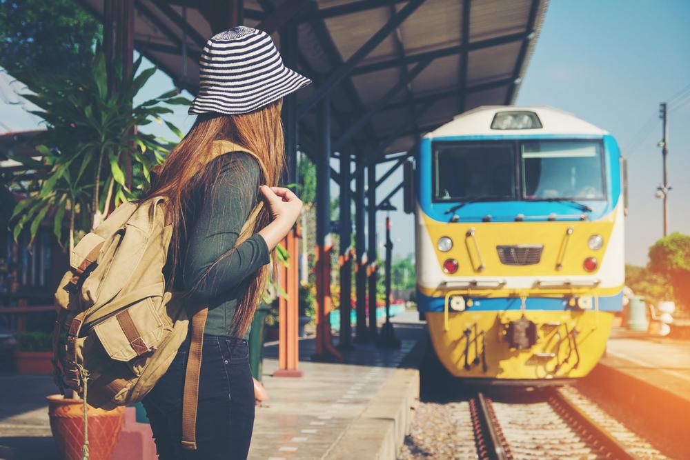 Ragazza che attende il treno alla stazione