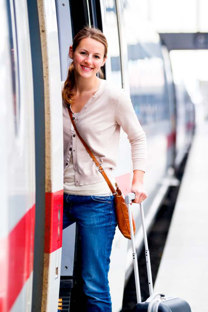Woman getting on train to airport with luggage