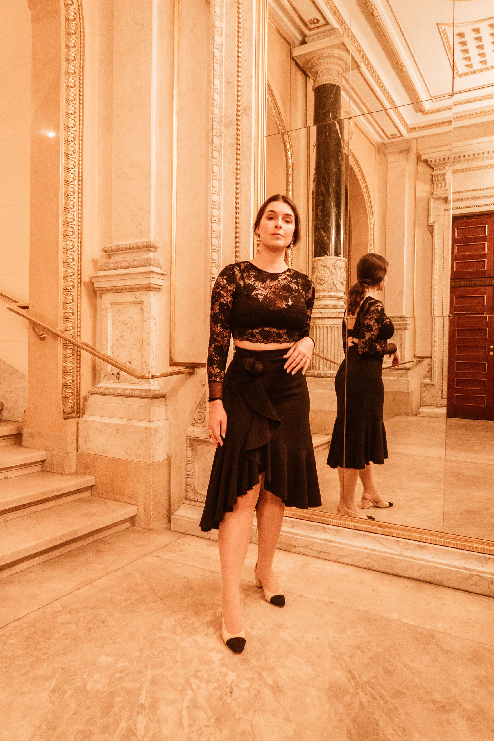 Arara Pintada wears long earrings and lace top with ruffled skirt and Chanel slingback for a night at the Vienna Opera
