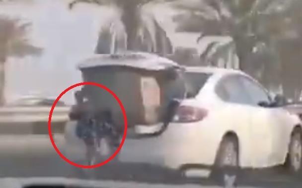 امرأة تجلس في صندوق سيارة سائرة على إحدى الطرق في البحرين