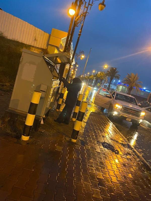 صورة لفني كهرباء يعمل تحت الأمطار بجازان لضمان استمرار الخدمة