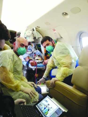 أطباء ينقلون مصاب كورونا بالإخلاء الطبي