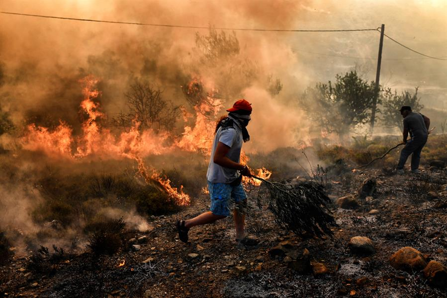 رجل يهرب من النيران شرق العاصمة اليونانية في 15 أغسطس وتم استدعاء الجيش لمساعدة رجال الإطفاء لإخماد حرائق مستمرة من 3 أيام في