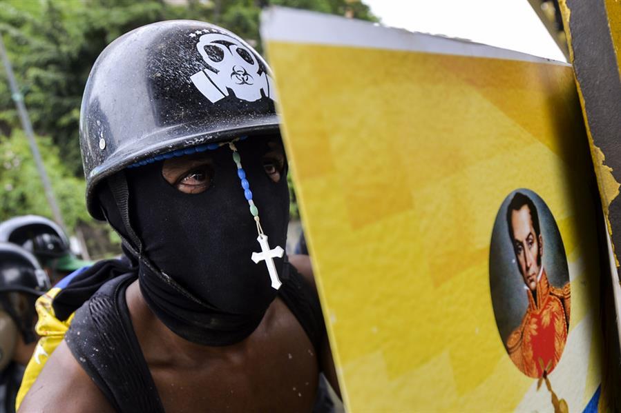 متظاهر معارض للرئيس مادورو خلال اشتباكات مع شرطة مكافحة الشغب في كراكاس بفنزويلا في 7 يونيو