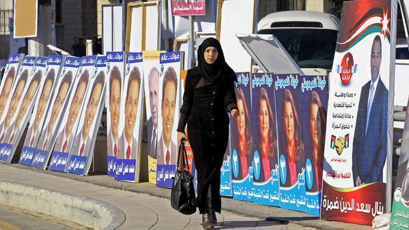 صورة الفتاة تسير بجوار الملصقات الانتخابية