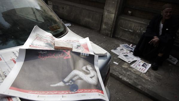 يجلس بجوار صحيفة مصرية في القاهرة الاثنين
