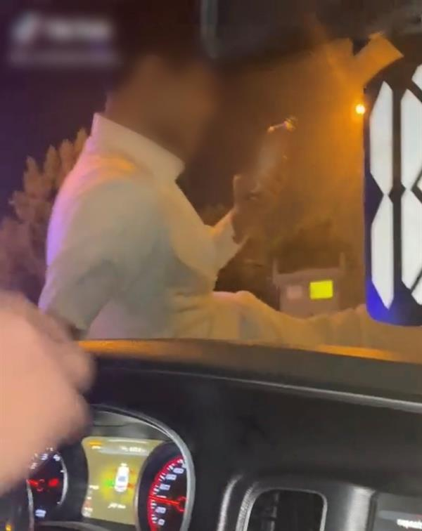 ضبط شخص قاد مركبته خلال جلوس آخر على غطاء محركها (صور)