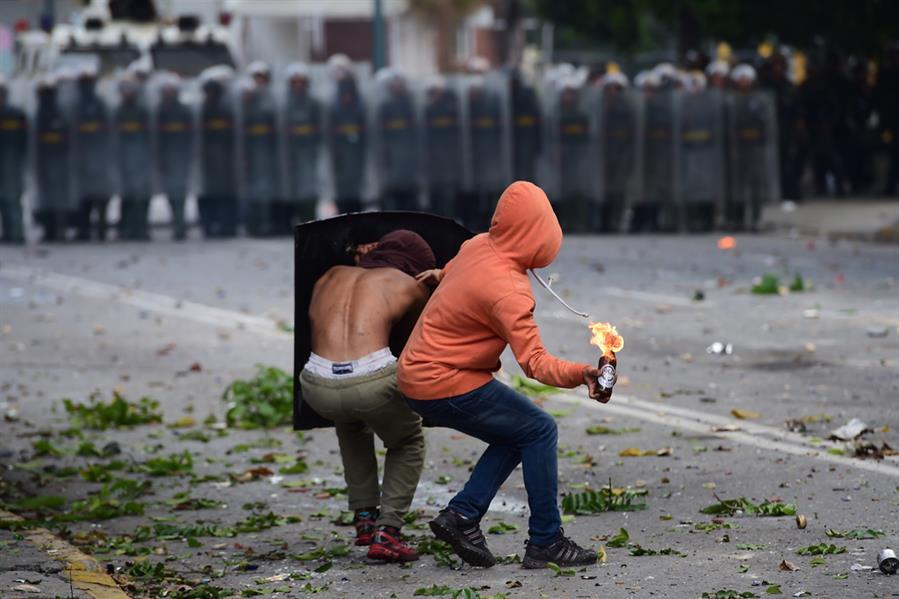 متظاهرون مناهضون للحكومة الفنزويلية يلقون زجاجات حارقة باتجاه عناصر الحرس الوطني خلال إضراب عام مدته 48 ساعة دعت إليه المعارضة