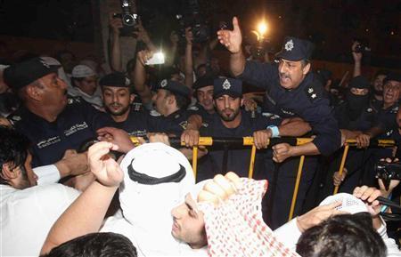 رجل شرطة يتحدث الى متظاهرين مناهضين للحكومة أمام البرلمان الكويتي