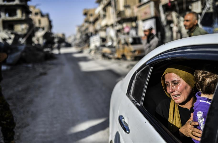 امرأة تبكي وهي تنظر بحسرة على منزلها المدمر بالرقة في 20 أكتوبر