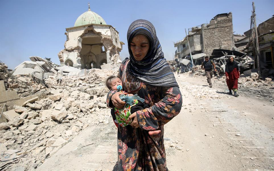 امرأة عراقية تحمل طفلا قرب مسجد النوري المدمر أثناء خروجها من مدينة الموصل العراقية في 5 يوليو أثناء هجوم القوات العراقية لاست