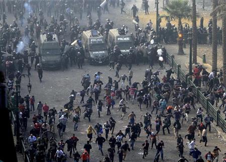 محتجون يجرون جراء اشتباكات مع شرطة مكافحة الشغب في ميدان التحرير بالقاهرة
