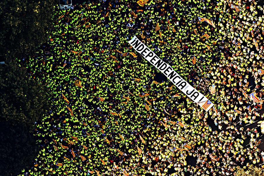 """صورة نشرتها المجلة الوطنية الكاتالونية في 11 سبتمبر لمتظاهرين في برشلونة يحملون لافتة عملاقة تقول """"الاستقلال الآن"""""""