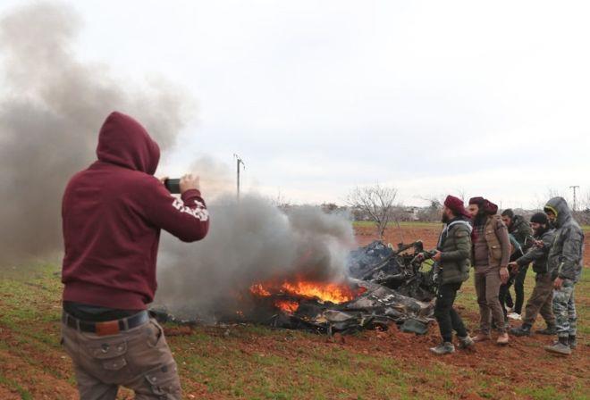 مقاتلون سوريون معارضون يتجمعون حول بقايا طائرة هليكوبتر