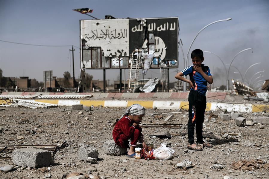 طفلان عراقيان وسط أنقاض شارع في حي نابلس بالموصل أمام لوحة تحمل شعار داعش في 12 مارس أثناء هجوم القوات العراقية لاستعادة الأجز