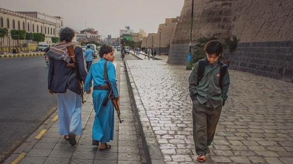 صورة تداولها يمنيون لطفل في طريق عودته من المدرسة بينما يمر بجوار مسلح وابنه الذي أثقله حمل السلاح