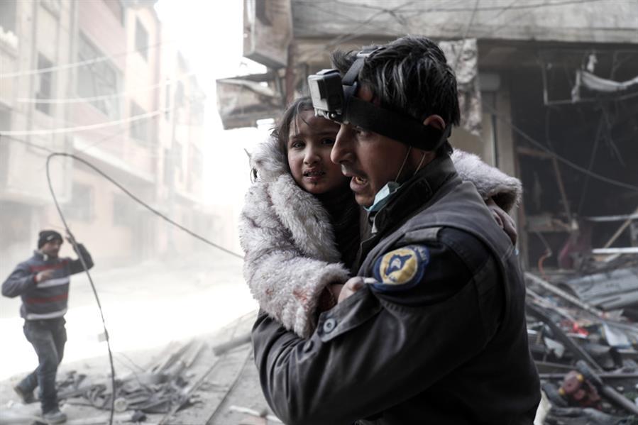 """متطوع في """"الدفاع المدني السوري"""" يحمل طفلة جريحة وسط الأنقاض عقب غارات جوية شنتها قوات النظام السوري على مدينة دوما شرق دمشق في"""