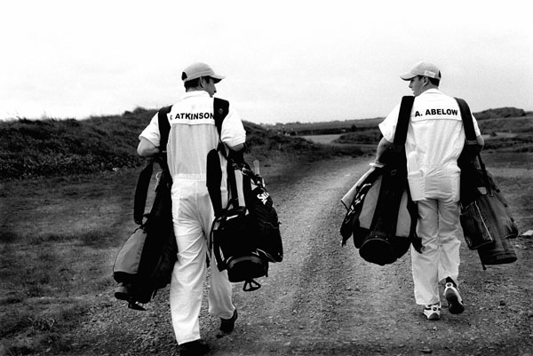 Two Doonbeg caddies carrying double bags-head to the practice ground (All images by Paul Marshall)