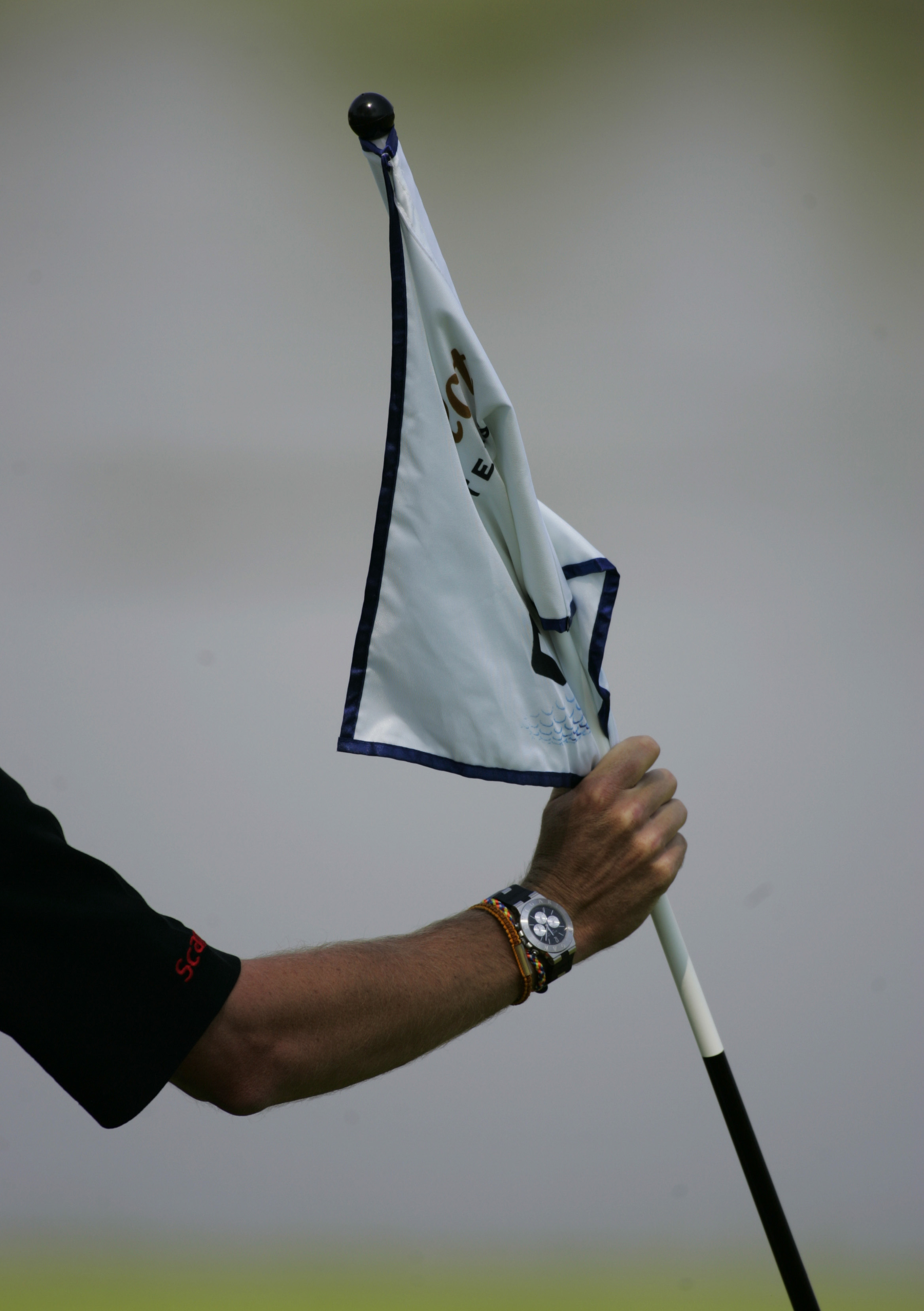 Rule 17-2: If an opponent or competitor attends, removes or holds up the flagstick during the stroke and might influence the ball's movement then they incur a penalty