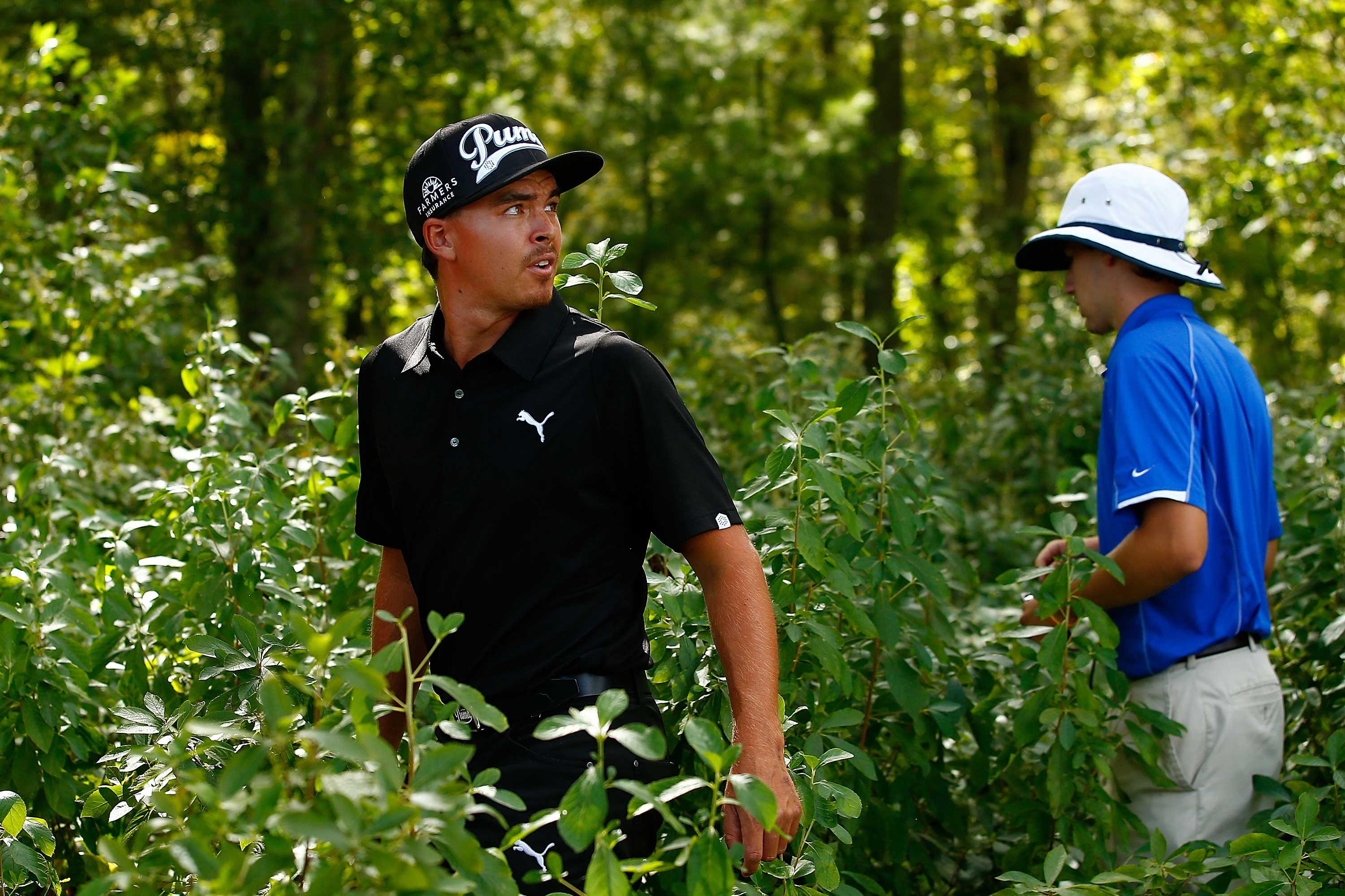 Rickie Fowler and a volunteer look for a ball at TPC Boston, venue of the Deutsche Bank Championship (Photo: Jared Wickerham/Getty Images)