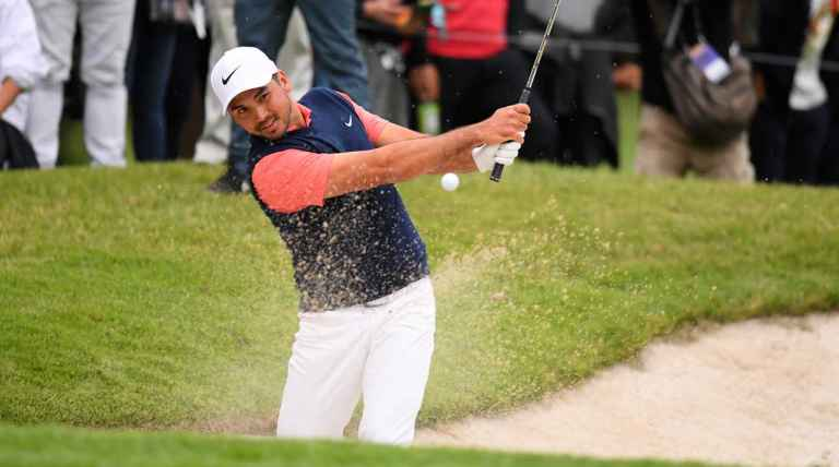Jason Day splashes out of a greenside bunker with a 6 iron