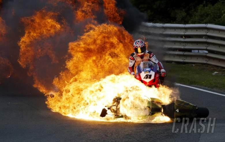 Vince Whittle`s bike on fire as Noriyuki Haga takes evasive action. All riders were ok.
