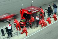 The Ferrari team relax on the pit wall as Rubens Barrichello drives past