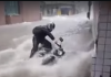 WATCH: Biker and bike washed down a flooded road