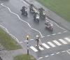 Biker helps old lady across road