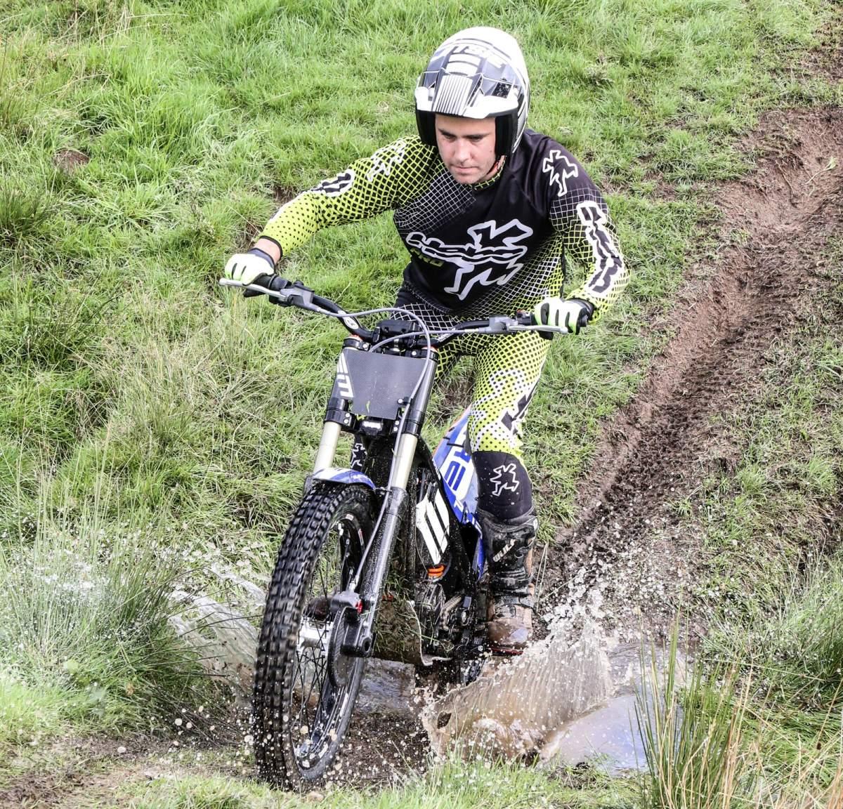 A trials bike crosses a stream