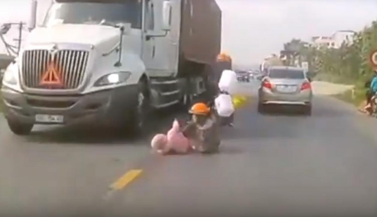 Mother saves baby after motorcycle crash in front of truck