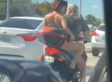 Woman shaves legs on moped