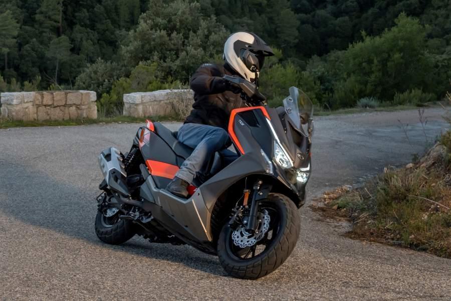 a maxi scooter rides upo a mountain road