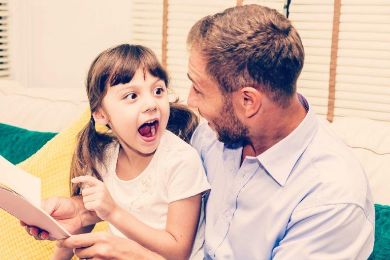 Niña se sorprende y señala un libro con su padre