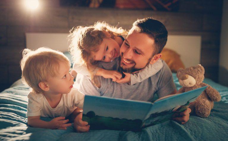 Niños leyendo un libro con su padre en la cama