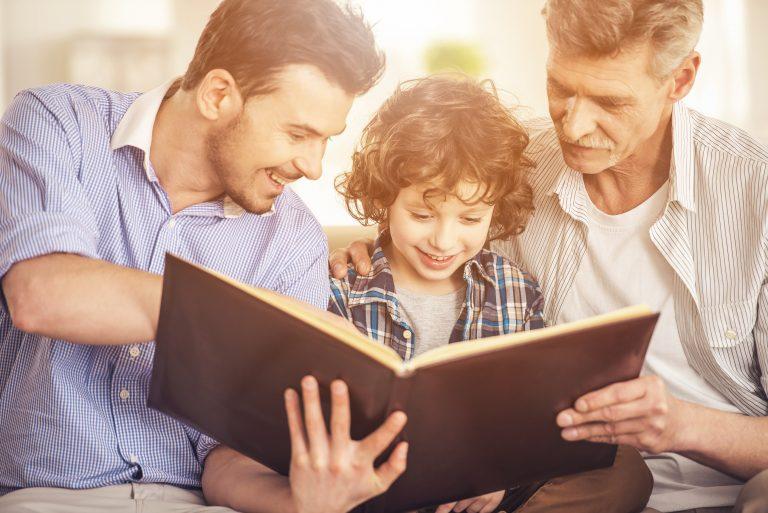 Niño leyendo un libro con su padre y su abuelo