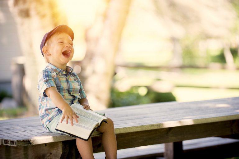 Niño riendo con un libro abierto