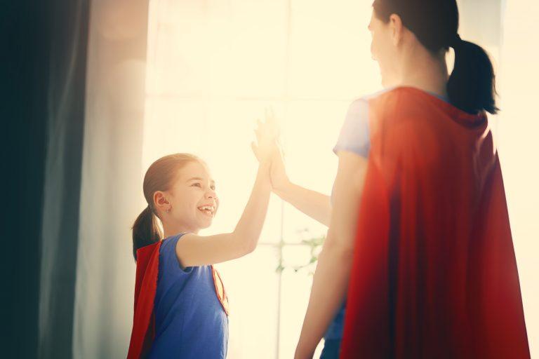 Madre e hijas chocan las manos con capas de superheroínas