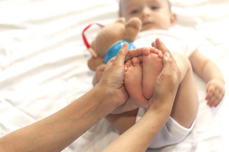 Unas manos unen los pies de un bebé