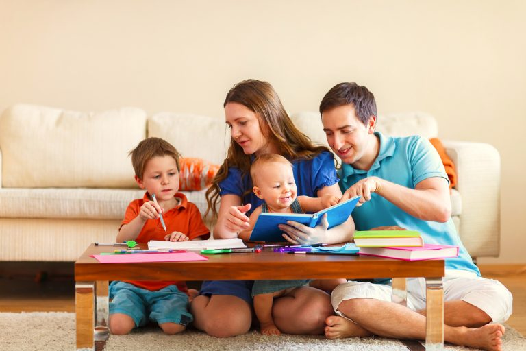 Young family with two kids drawing and reading together