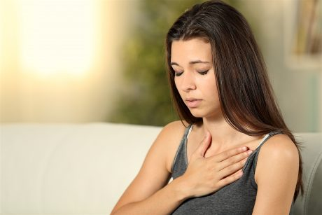 Girl Having Respiration Problems Touching Chest Sitting On A Couch In The Living Room At Home