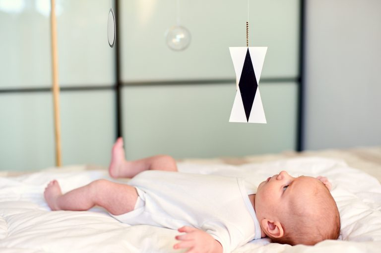 Adorable Baby Boy Infant In White Sunny Bedroom Lying And Looks At Munari Montessori Mobile.