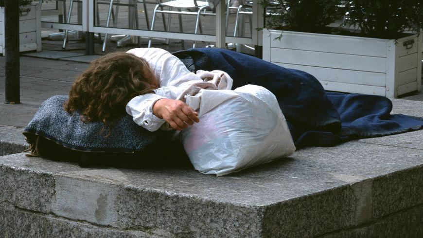 Une femme seule qui dort dans la rue près d'un café (photo d'illustration)