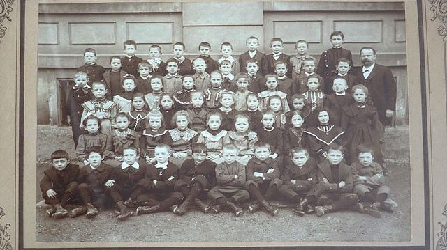 Photo d'une classe vers 1880. L'instituteur et 56 élèves mixtes. Photographe anonyme, lieu indéterminé. Cliché 20,5 cm x 14,5 c