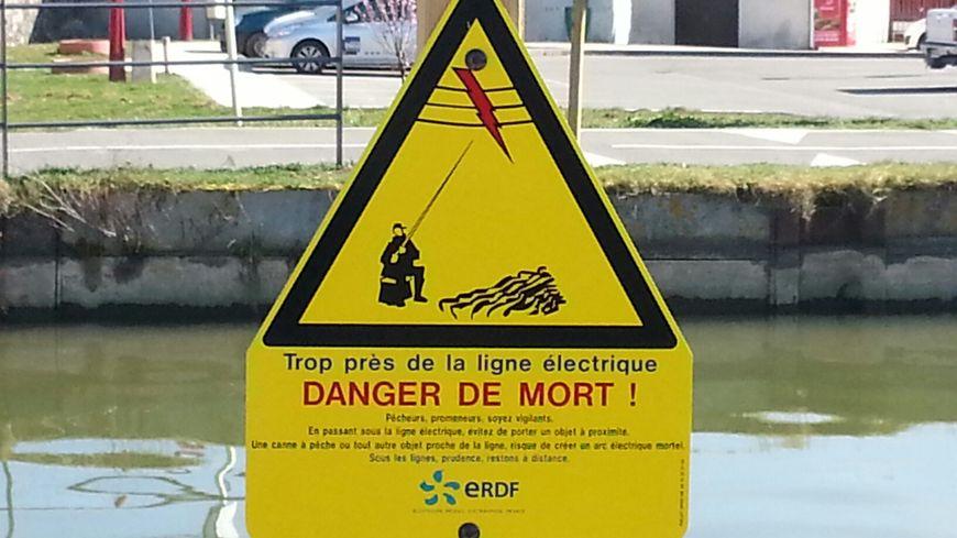 Panneau d'avertissement au danger des lignes électriques pour les pêcheurs le long du canal du Rhône au Rhin à Froidefontaine