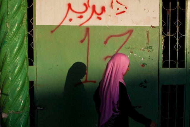 Une jeune femme passe devant un graffiti annonçant le début de la révolution (Lybis, 2012)