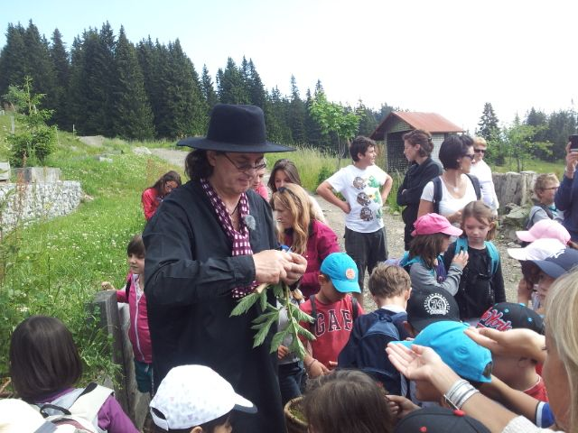 Le chef cuisinier Marc Veyrat, l'homme au chapeau noir, apprend aux enfants les bienfaits des plantes de montagne. - Radio France