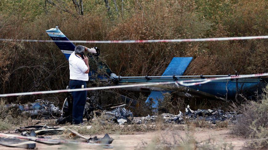 """Un enquêteur autour de la carcasse d'un des hélicoptères qui se sont écrasés lors du tournage de l'émission """"Dropped"""""""